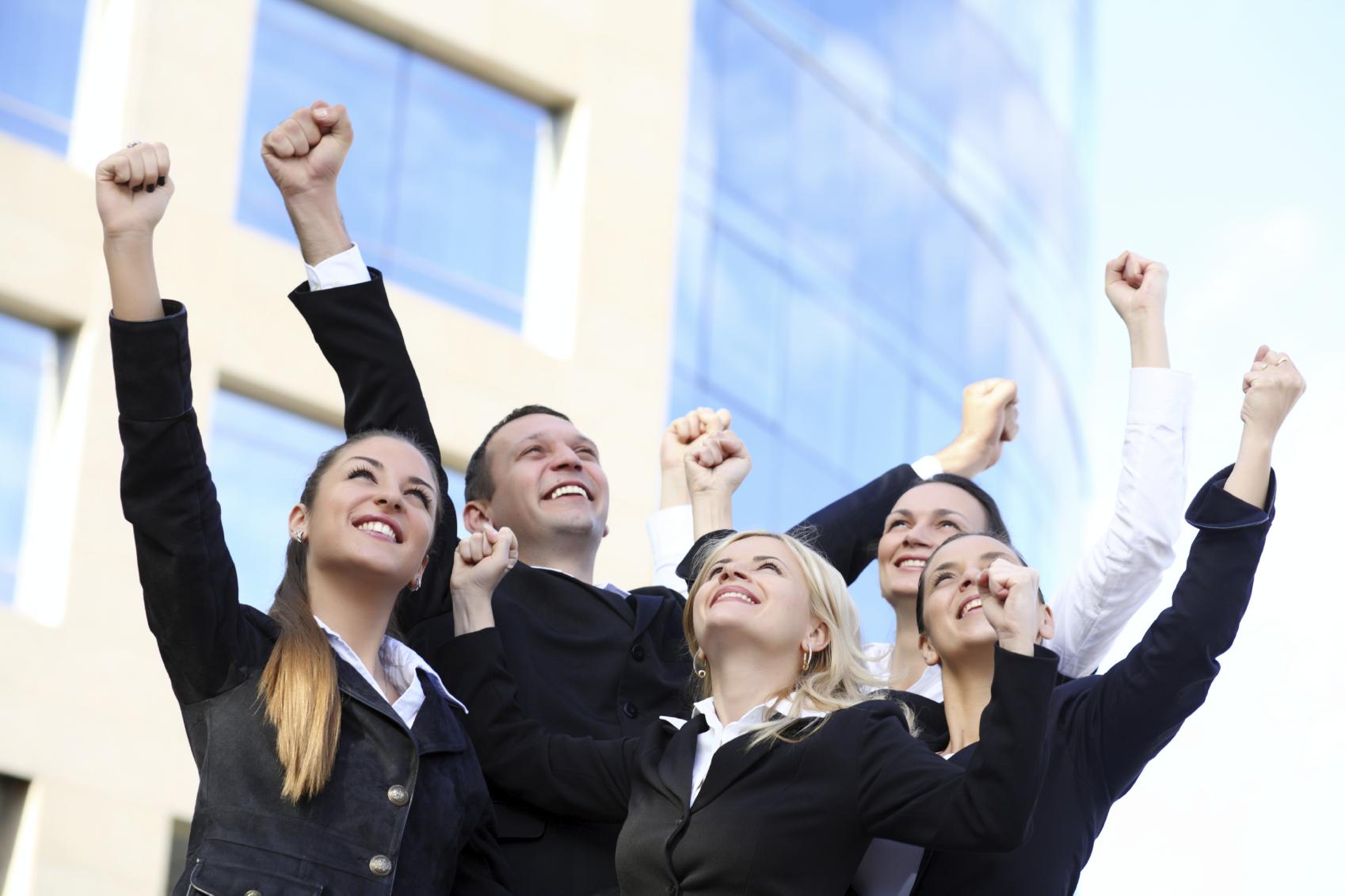 Successful businesspeople raising hands upward.