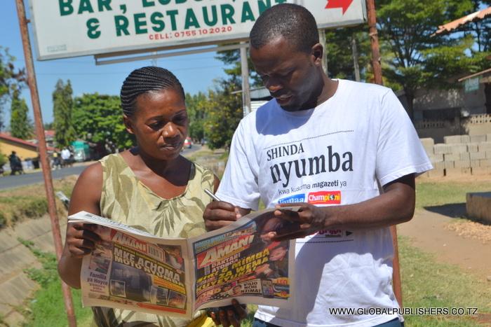1.Debora Muhagama (kushoto) akisaidiwa kujaza kuponi yake na Ofisa Masoko wa Global,Yohana Mkanda.