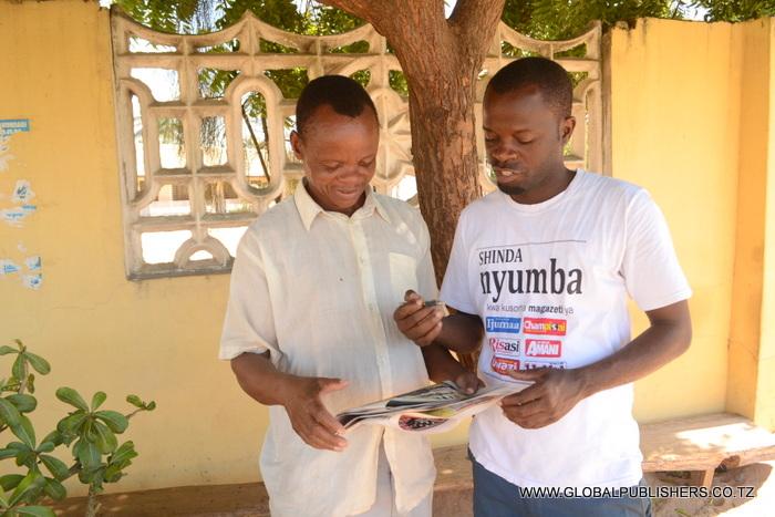 5.Mkanda (kulia) akimfafanulia jambo msomaji wa gazeti la Amani namana ya kushiriki bahati nasibu hiyo.