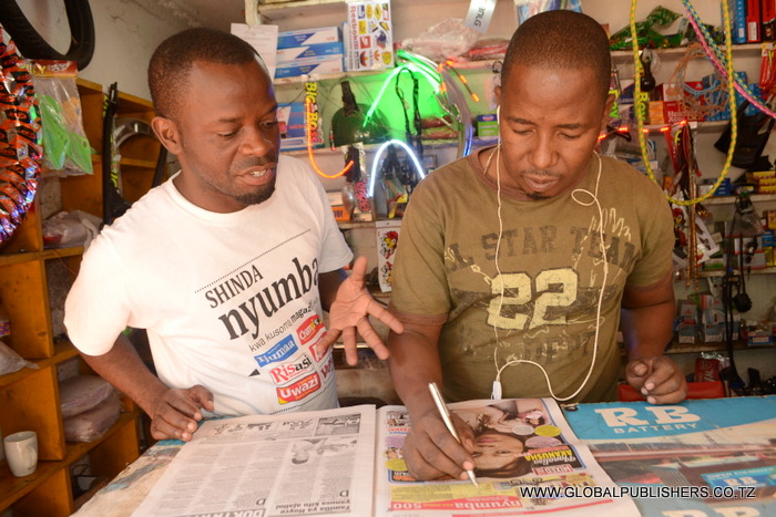 7.Msomaji wa gazeti la Amani mkazi wa Kunduchi Dar (kulia) akijaza kuponi.