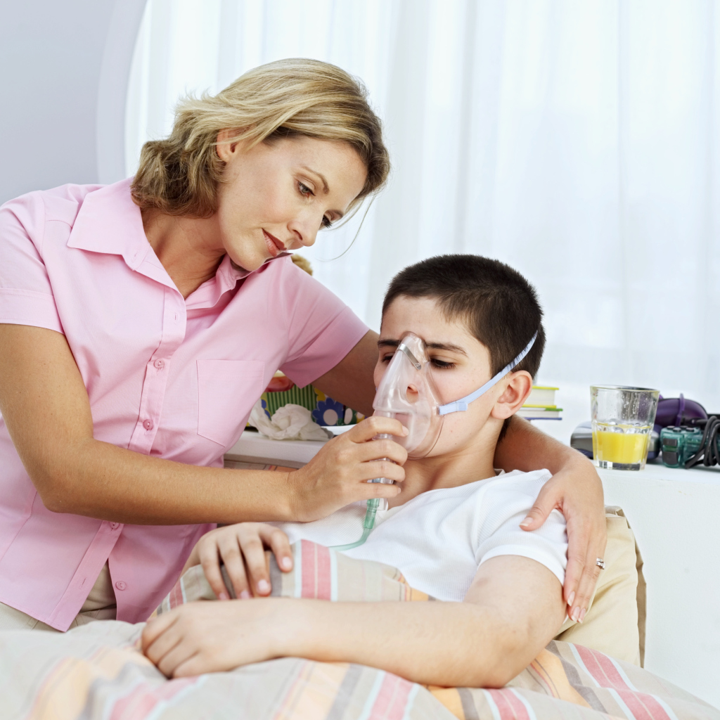 A mother holding an oxygen mask for her son (10-12)